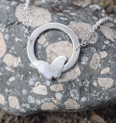 silversmycke med fjäril på spräcklig sten utomhus