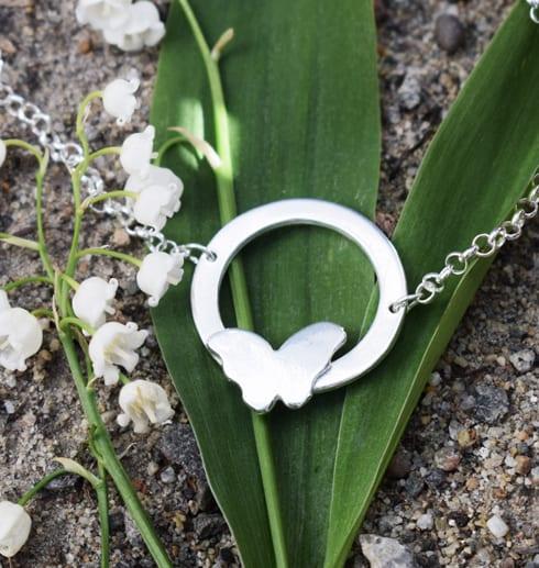 Silversmycke med fjäril på liljekonvaljer utomhus