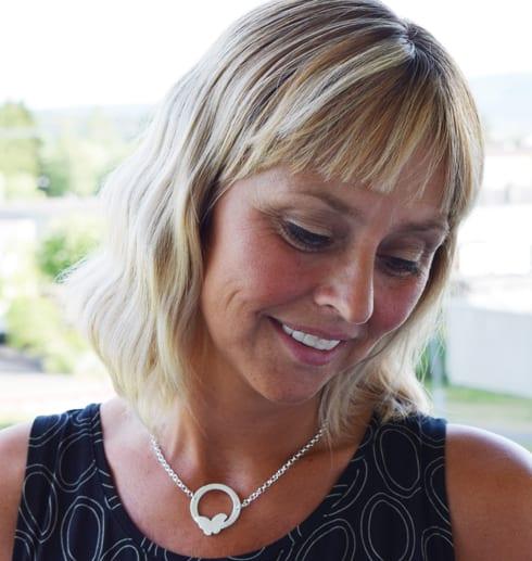 silverhalsband runt halsen på kvinna utomhus