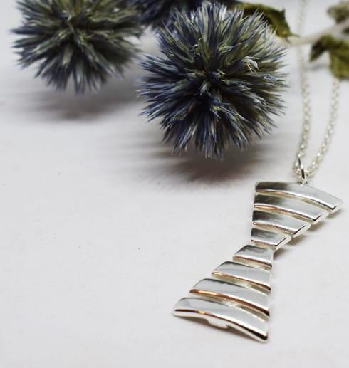 Halsband i silver i form av ett ensmärka mot vit bakgrund med blå blomma