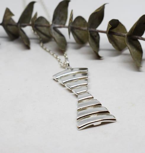 silversmycke i form av ett ensmärke mot vit bakgrund med en grön kvist