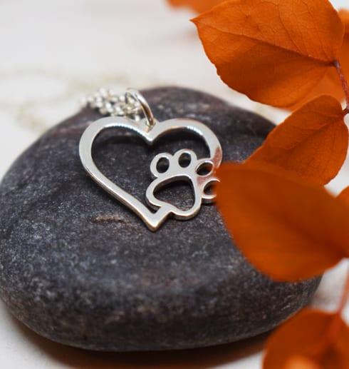 hjärta i silver med tass på mörkgrå sten med en orange kvist på sidan