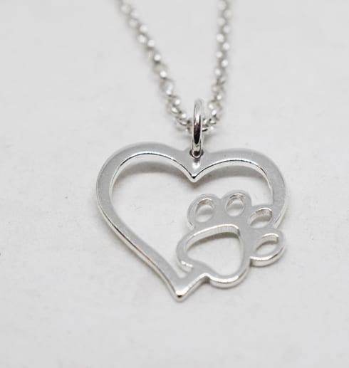 silversmycke i form av ett hjärta med en tass på vit bakgrund