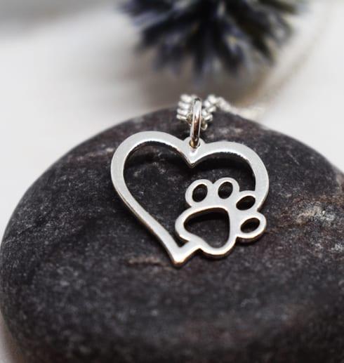 hjärta med tass i silver på mörkgrå sten med blå blomma i bakgrunden