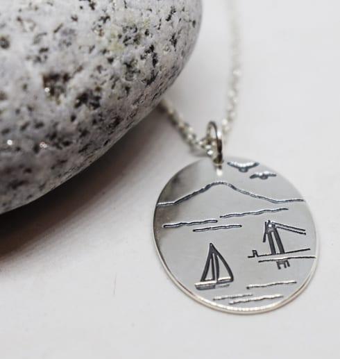 ovalt silversmycke mot vit bakgrund och gråvit sten på sidan
