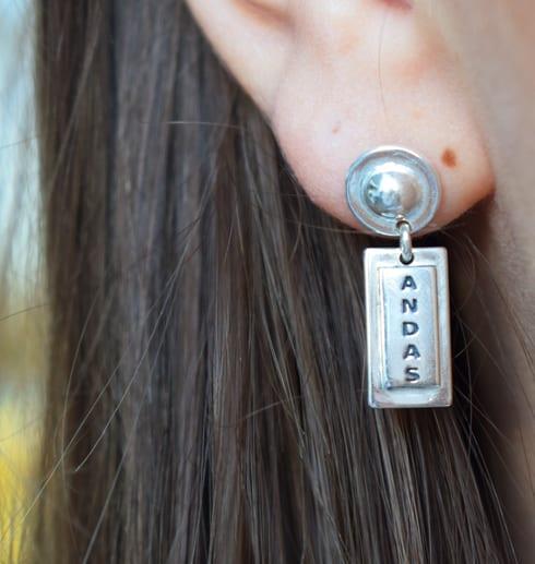 Silverörhänge med texten ANDAS på ett öra