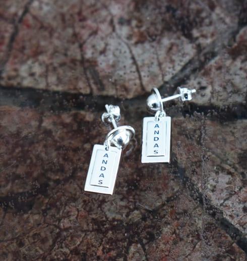 Silverörhängen med texten ANDAS på brungrå betong