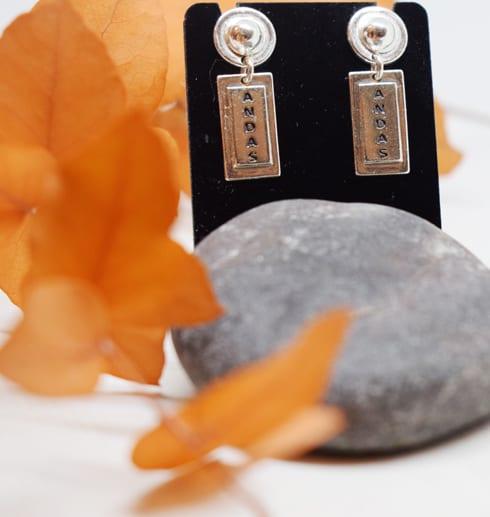 rektangulära örhängen på svart upphäng med grå sten och blad i orange