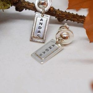 rektangulära silverörhängen med texten ANDAS på en stam och orange löv