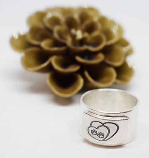 Bred silverring med tassar på mot vit bakgrund och blomma