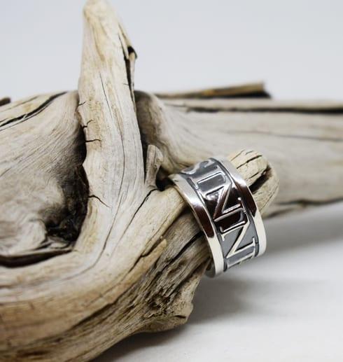 silverring med text på svart botten på trädgren