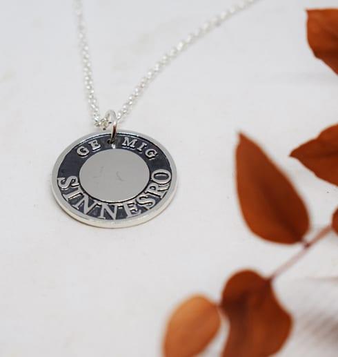 silversmycke med text på vit bakgrund med orange kvist