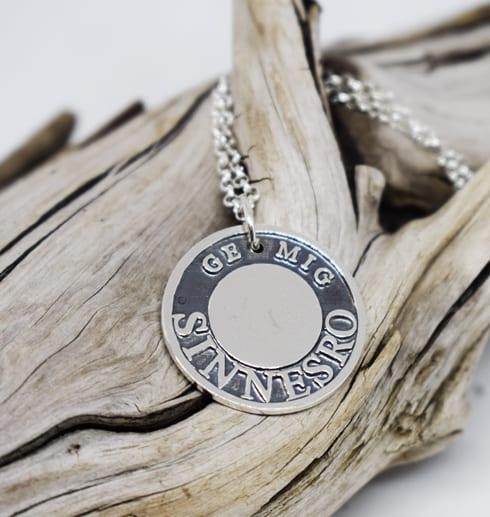 silversmycke med text på trädgren