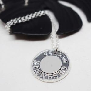 silversmycke med text på vittb botten med svart metallöv bakom