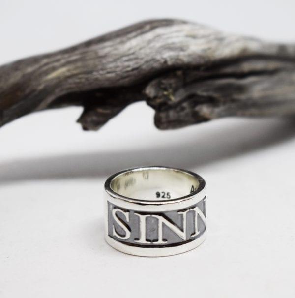 silverring med text med svart botten på vit bakgrund med trädgren bakom