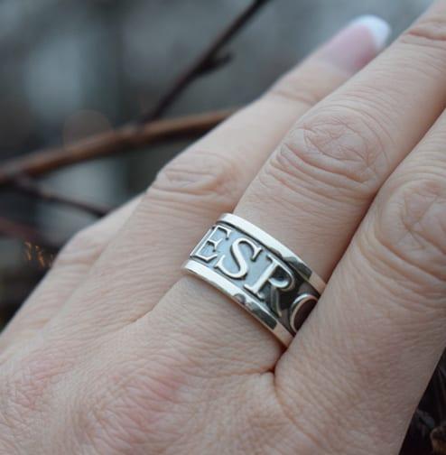 silverring med text på svart botten på finger utomhus