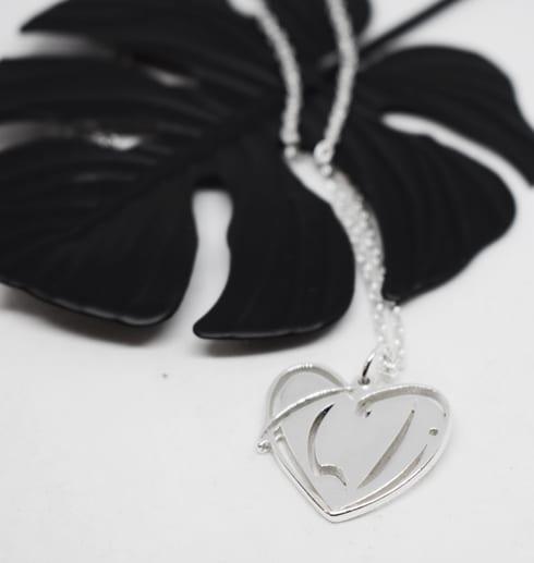 silverhalsband i form av ett hjärta på vit botten med en svart metallblomma bakom