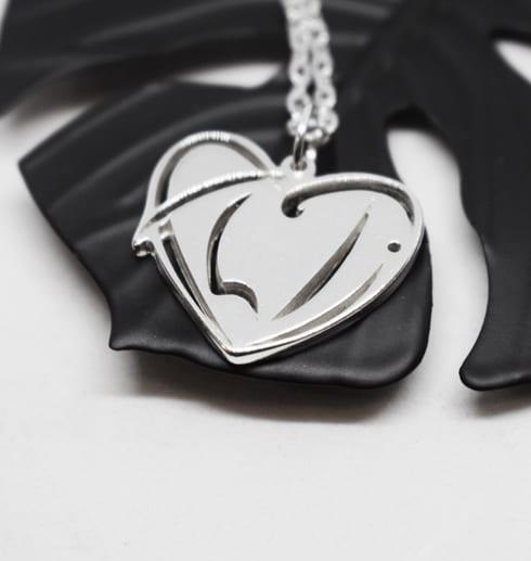 silversmycke i form av ett hjärta på svart metallblomma