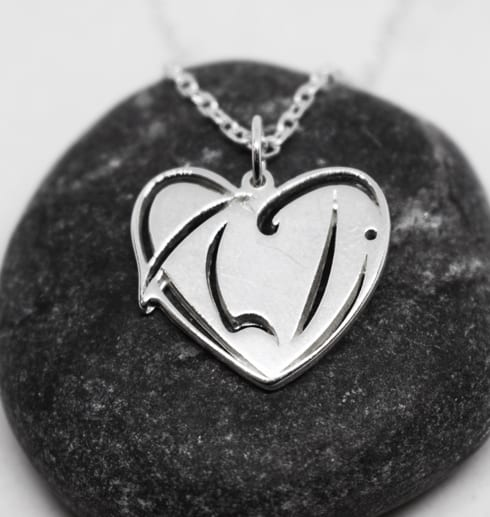 silversmycke i form av ett hjärta på en mörkgrå sten