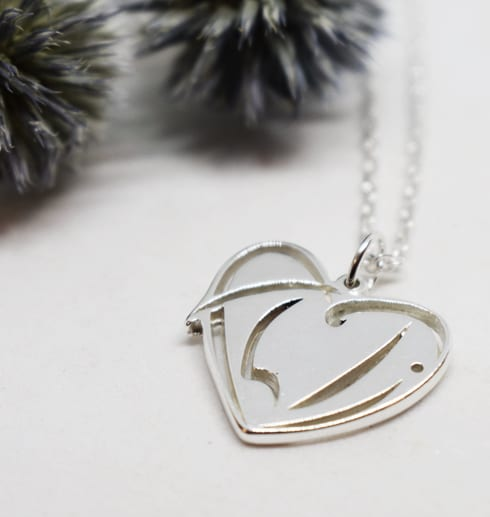 silversmycke i form av ett hjärta på vit bakgrund med blå blommor bakom