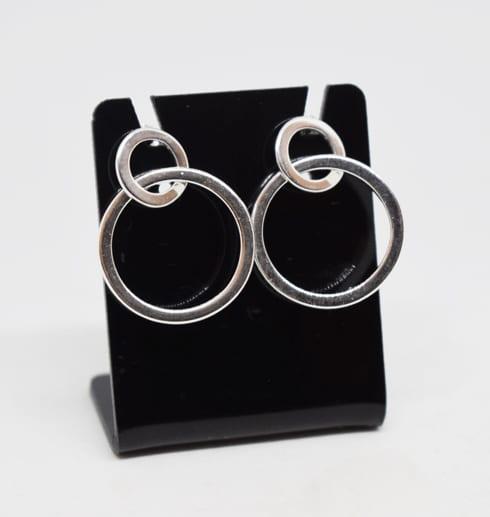 silverörhängen som sitter på en svart hållare med vit bakgrund
