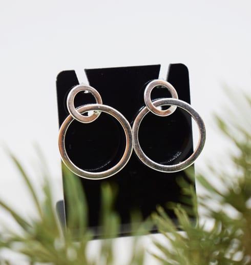 silverörhängen i form av ringar påen svart hållare med granris framför