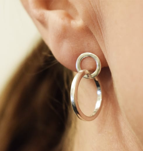 silverörhängen i form av ringar som sitter på ett öra