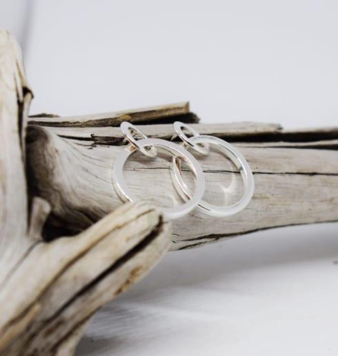 silverörhängen i form av ringar som ligger på en trädgren