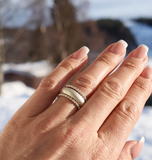 tre silverringar på finger utomhus i solen