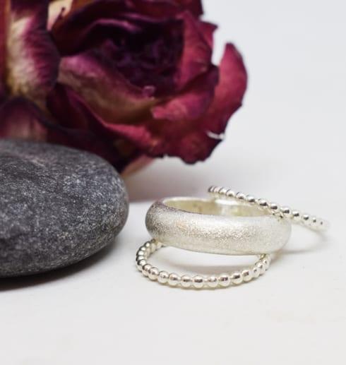 tre silverringar på vit botten med grå sten och ros bredvid