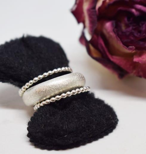 tre silverringar på svart sammetshållare med ros bakom