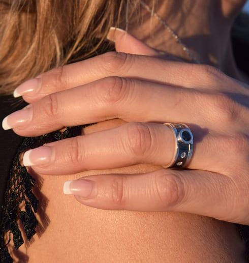 silverring med stor svart sten och små vita stenar på svartoxiderad botten på hand på kvinna utomhus i solen