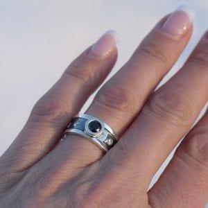 silverring med stor svart sten och mindre vita stenar på svartoxiderad botten på finger utomhus