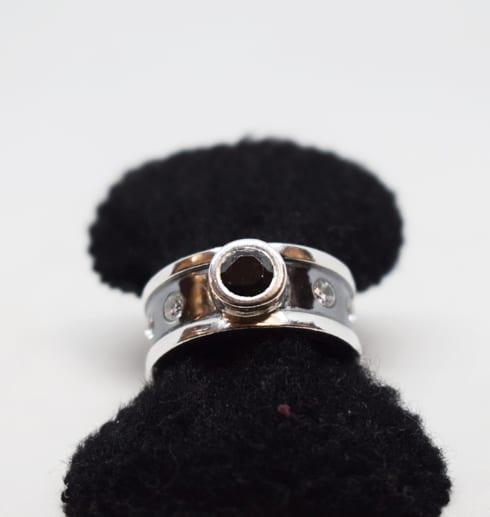 silverring med stor svart sten och mindre vita stenar på svartoxiderad botten som sitter på en svart sammetsringhållare