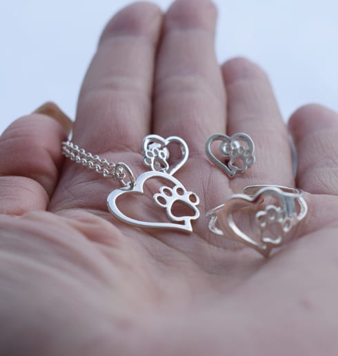 Hand med silversmycken i form av hjärtan med tass utomhus