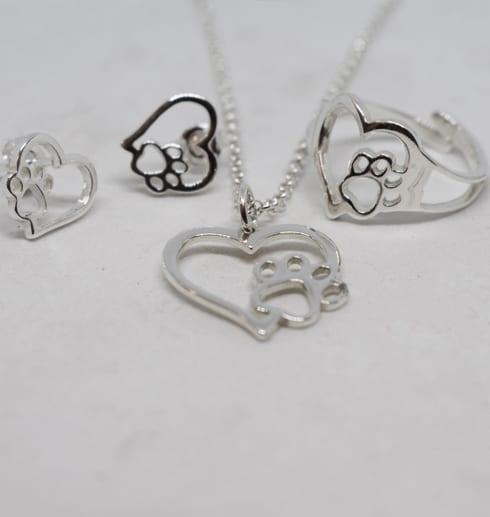 silversmycken i form av hjärta med tass med vit bakgrund