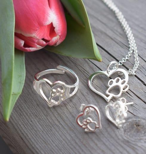 silversmycken i form av hjärtan med tass på trä utomhus med en tulpan bredvid