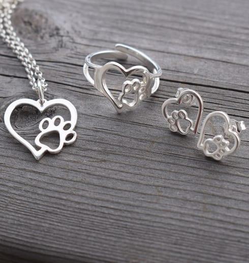 silversmycken i form av hjärta och tass på trä utomhus