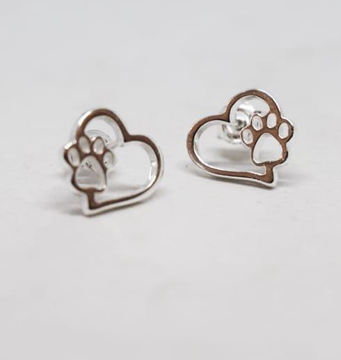 silverörhängen i form av ett hjärta med en tass på vit bakgrund