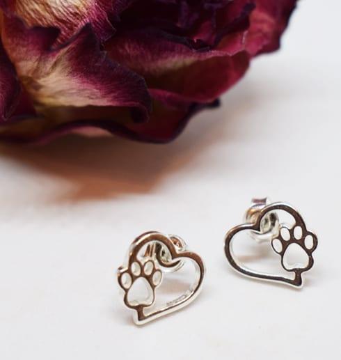 silverörhängen i form av hjärtan med tass på vit botten med ros bakom