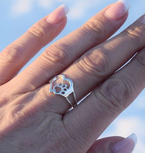 silverring i form av ett hjärta med en tass på ett ringer utomhus i solen