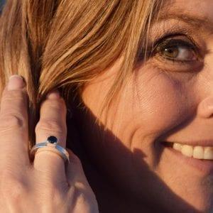 kvinna med silverring med svart sten på fingret utomhus i solen