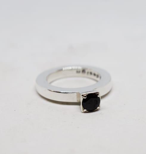 silverring med stor svart sten på vit bakgrund