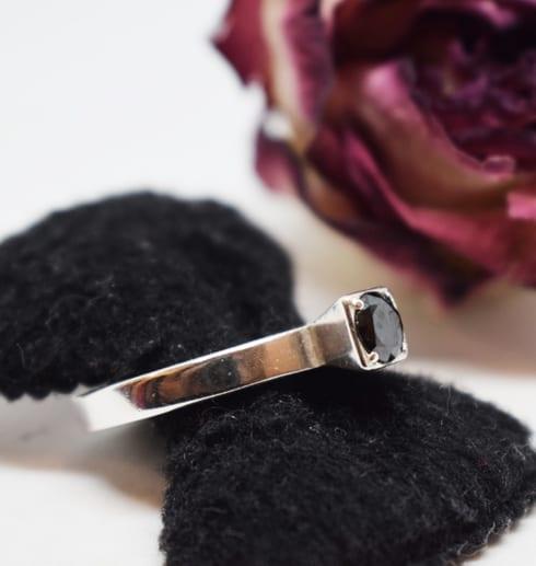silverring med svart sten på svart sammetsringhpllare och lila ros i bakgrunden