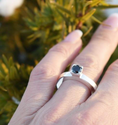 silverring med svart sten på firnger utomhus i solen vid enbuske