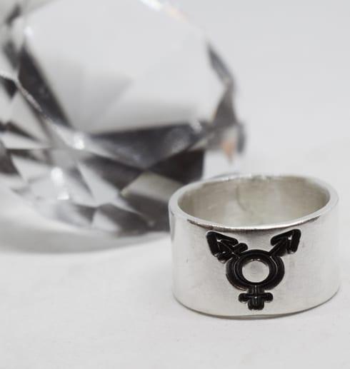 bred silverring med transgendersymbol på vit botten med stor glasdiamant bakom