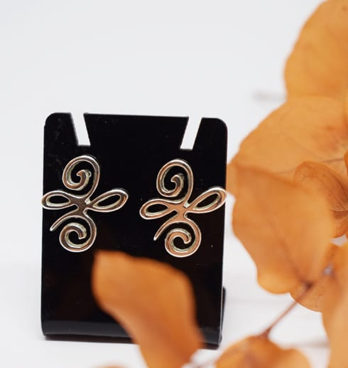 silverörhängen på svart hållare med orange kvist