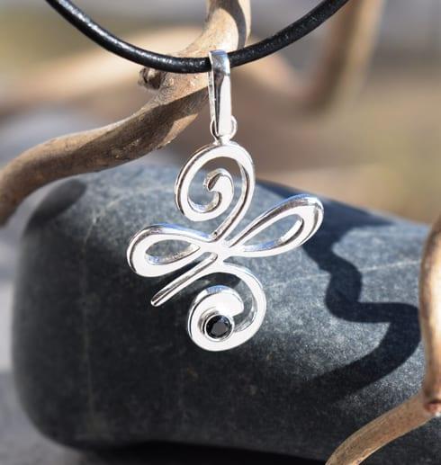 silversmycke i läderrem utomhus med grå sten och trädgren bakom
