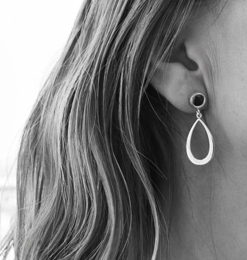 droppformade silverörhängen på kvinnas öra, svartvit bild