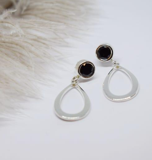 droppformade silverörhängen med svart sten på vid botten med en beige strutsfjäder bredvid